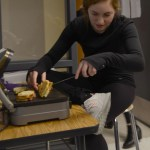 Sophomore Emma Broaddus checks on the sandwiches that she is putting together for her classmates. Photo by Grace Goldman