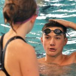 Freshman Matthew Roth explains proper technique to a new swimmer. Photo by Libby Wilson