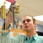 Senior Phillip Fuson summons a bird out of its cage. Photo by Ellie Thoma