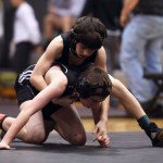 Freshman Charlie Voyset pins his opponent on the mat during his last match. Photo by Morgan Browning