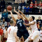 Senior Trevor Thompson attempts to make a basket while being blocked by his opponents. Photo by Maddie Smiley