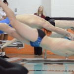 Sophomore Aaron Berlau (lane 1) and senior Jeremy Martin (lane 4) dive into the pool. Photo by CJ Manne
