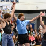 Senior Isaac Schmidt holds Seniors Fabrizzio Bortolotti and William Schmidt's hands in the air in triumph. Photo by Ellie Thoma