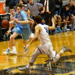 Junior Jack Schoemann dribbles down the court. Photo by Luke Hoffman