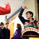 Junior Matthew Trecek high-fives students as he invites them into the Chinese room. Photo by Ellie Thoma