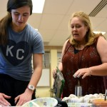 Ms. Anderson gives advice to junior Madeline Hlobik on how to properly craft her sushi roll. Photo by Ellie Thoma