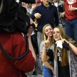 Seniors Allie Libeer and Hope Dunn pose as a news reporter films the student sections. Photo by Ellie Thoma