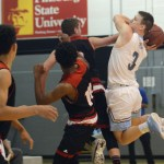 Senior Trevor Thompson attempts a lay-up as Lawrence players foul him. Photo by Ty Browning