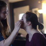 Sophomores Sophia Scarlett and Camille Vandergriff do each others make up before the dance. Photo by Morgan Plunkett