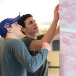 Juniors Reser Hall and Thomas Sweat set up the pink fabric around the cafeteria as they talk with each other. Photo by Morgan Plunkett