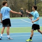 Sophomore Oliver Broce and freshman Adam Jolles high five after their sweeping victory against their opponents in their match. Photo by Luke Hoffman