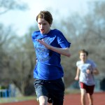 Sophomore Quincy Eastlack sprints into the finish line of his 400 meter time trial. Photo by Luke Hoffman