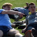 Junior Ian Schutt and sophomore Bradley stretch their hamstrings and goof around during track and field warmups. Photo by Katherine Odell