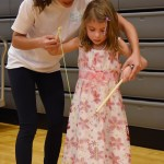 Freshman Sophie Sun teaches a young girl how to yo-yo. Photo by Diana Percy