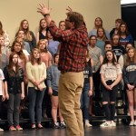 """Choir director Ken Foley signals for the alto section to sing louder in order to over power the baritones during """"Hallelujah"""". Photo by Lucy Morantz"""