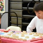 Junior Brian Li plays a traditional Chinese board game with a little boy. Photo by Laini Reynolds