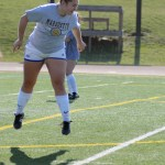 Junior Grace Chisholm practices head bumping the ball during a warm ups. Photo by Ellen Swanson