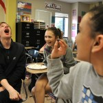 Sophomore Luke Knopke prepares to catch a bluberry in his mouth as sophomore Maggie Mulligan throws it. Junior Mia Vaught laughs in reaction to her classmates. Photo by Grace Goldman