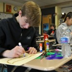 Using a marker, sophomore Luke Knopke colors the outline of his Mardi Gras mask. Photo by Grace Goldman