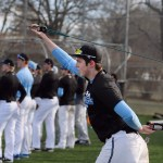 Junior Matt Hicks stretches his shoulders while watching the varsity practice. Photo by Kaitlyn Stratman