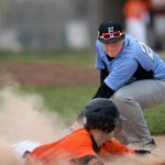 Junior Nick Wohler attempts to tag his opponent as he slides into third base, but the Northwest player is safe. Photo by Kaitlyn Stratman