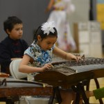 A little girl performs with her group on Guzhengs, traditional Chinese instruments. Photo by Morgan Plunkett