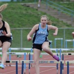Freshman Aislinn Kinsella (Middle), sophomore Annabelle Cook (Right), and freshman Jannie Mahaffy run the 100 hurdles. Photo by CJ Manne