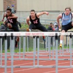 Sophomore Micheal Perry jumps over the hurdle trying to avoid hitting it, while running as fast as he can to beat his opponents. Photo by Katherine Odell