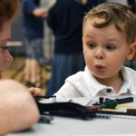 """A chid attending """"The Giving Bricks"""" station at the fair plays with legos. Photo by Diana Percy"""