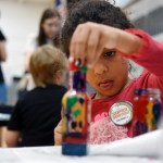 """A young girl paints a bottle at the """"Serve Community Church"""" table. The tape provided a place for children attending the fair to express themselves creatively with paint and glass bottles. Photo by Diana Percy"""