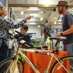 A member of the Ride KC organization discusses bikes with a woman at his booth. Photo by Diana Percy