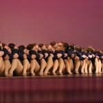 """The Varsity girls sit in their starting position as they turn their heads in groups once the music of their lyrical routine, """"Stubborn Love"""" by The Lumineers, cues them. Photo by Lucy Morantz"""