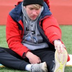 Sophomore Micheal Perry stretches before his hurdle jump event. Photo by Audrey Kesler