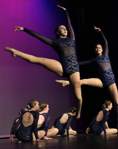 Sophomore Hannah Goettsch and senior Hayley Bell leap over their teammates during the varsity team's lyrical routine. Photo by Lucy Morantz