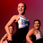 Junior Emma Renwick flashes a smile at the audience while performing in the varsity team dance. Photo by Maddie Smiley