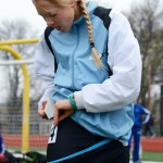 Junior Ingrid Worth places a stickered number to her shorts so she can be identified on the track.  Photo by Annie Lomshek