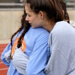 Sophomore Lucy Hoffmann hugs junior Madeline Hlobik after she finished the first leg of the 4X800 relay. Hlobik, nervous before running, ended up with the second fastest time in her relay group. Photo by Annie Lomshek