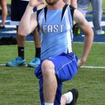 Sophomore Garrett Boschen does lunges as he warms up for the 100 meter dash. Photo by Laini Reynolds