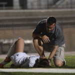 After getting hurt sophomore Emily Cooper is comforted by Coach Jamie Kelly. Photo by Katherine Odell