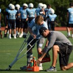 Junior Griffin Fries and tackle and tight end coach, Brandon May  get together water bottles for the teams. Photo by Audrey Kesler