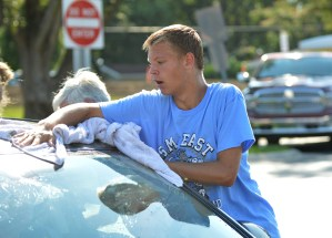 Freshman Tyler Debey dries the windshield of a car. Photo by Ally Griffith