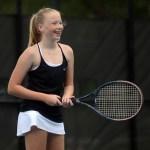 Freshman Elizabeth Mikkelson smiles as she prepares to return the serve.  Photo by Hadley Hyatt