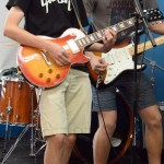 Senior Cal Knabe plays guitar onstage next to his bandmate senior Sam Fay. Photo by Katherine McGinness