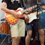 Senior Cal Knabe plays guitar onstage next to his bandmate senior Sam Fay. Photo by Katherine McGinness