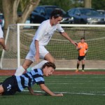 Junior Zach Bass takes a fall while Sophomore T.J. Libeer chases the ball. Photo by Aislinn Menke