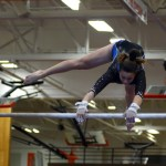 Sophomore Brooklyn Beck makes her handstand pirouette on the low bar during her routine. Photo by Aislinn Menke