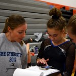 At the end of the competition, sophomore Abby Gorman and Coach Terflinger anxiously add up all the girl's scores to see how East placed at the meet. Photo by Aislinn Menke