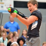 Senior Zach Yeo attempts to shoot an apple off another football player's head during the talent competition. Photo by Ally Griffith