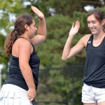 Seniors Caro Bush and Grace Chisholm high five after winning point in their doubles match. Photo by Ally Griffith
