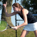 Senior Caro Bush signals to her doubles partner, Lidia Ragland, that the serve was out. Photo by Luke Hoffman